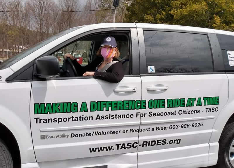 A woman with a mask is driving a van with the wording: Making a Difference One Ride at a Time